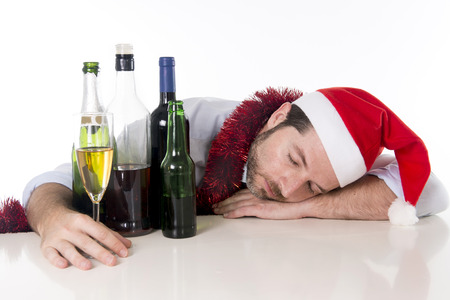 after the party: drunk business man in Santa hat with alcohol bottles and champagne glass sleeping after drinking too much at christmas party isolated on a white