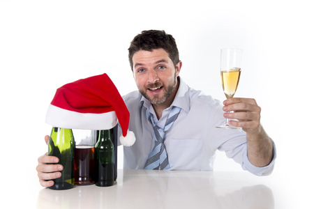 drunk business man with alcohol bottles in Santa hat holding champagne glass happy after drinking too much at christmas party isolated on a white