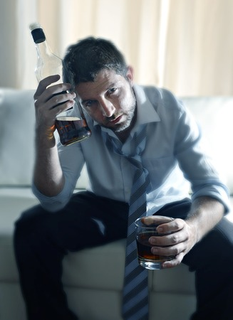 Attractive drunk business man at home sitting on couch at living room wasted  holding whiskey bottle against forehead in alcoholism problem photo