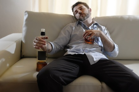 alcohol abuse: drunk business man at home lying asleep on couch sleeping wasted  holding whiskey bottle in alcoholism problem , alcohol abuse and addiction concept looking grunge and sick in edgy radical studio lightning