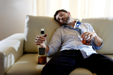 drunk business man at home lying asleep on couch sleeping wasted  holding whiskey bottle in alcoholism problem , alcohol abuse and addiction concept looking grunge and sick in edgy radical studio lightning