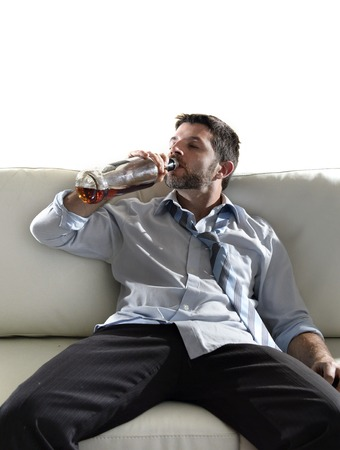 wasted: Attractive drunk business man sitting on couch wasted  drinking whiskey directly from bottle in alcoholism problem , alcohol abuse and addiction concept looking grunge , messy and sick with edgy studio lightning  Stock Photo