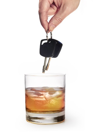 drink responsibly: man hand holding car keys over glass of whiskey isolated on white background representing safety and about the danger of drinking alcohol and driving drunk