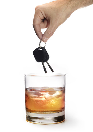man hand holding car keys over glass of whiskey isolated on white background representing safety and about the danger of drinking alcohol and driving drunk photo