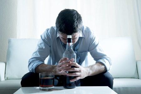 drunk: caucasian businessman alcoholic wearing a blue work shirt Stock Photo