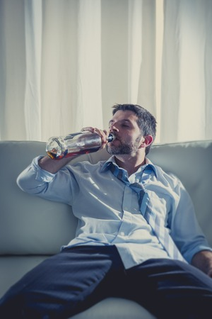 caucasian businessman alcoholic wearing a blue work shirt and tie drunk and drinking  Scotch or Whisky sitting on a sofa at home after a long day or week of work on a white background   photo
