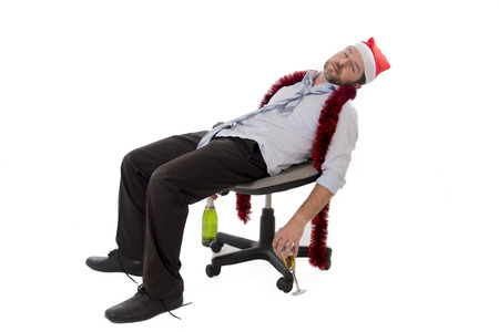 Happy drunk businessman wearing a santa hat with tinsel around his neck in a blue business shirt and blue tie holding a bottle and glass of champagne drinking sitting in a business office chair at his christmas party on white background