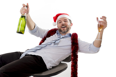 Happy drunk businessman wearing a santa hat with tinsel around his neck in a blue business shirt and blue tie holding a bottle and glass of champagne drinking sitting in a business office chair at his christmas party on white background photo