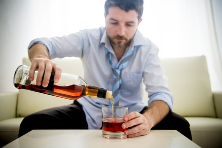 caucasian businessman alcoholic wearing a blue work shirt and tie drunk and drinking  Scotch or Whiskey sitting on a sofa at home after a long day or week of work on a white background.  photo
