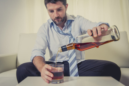 addictive drinking: caucasian businessman alcoholic wearing a blue work shirt and tie drunk