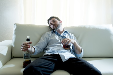 addictive drinking: caucasian businessman alcoholic wearing a blue work shirt  Stock Photo