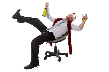 Happy drunk businessman wearing a santa hat with tinsel around his neck in a blue business shirt Stock Photo