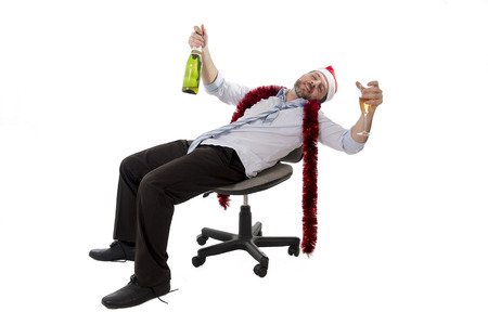 champers: Happy drunk businessman wearing a santa hat with tinsel around his neck in a blue business shirt