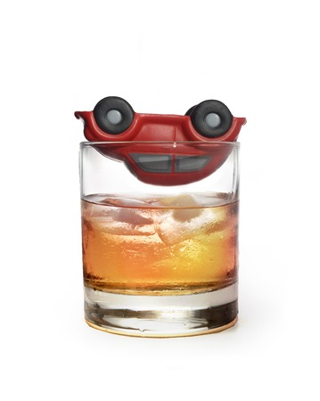drinking driving: toy car upside down on top of glass of whiskey as if it had a crash accident  isolated on white background representing safe driving and warning the danger of drinking alcohol and beeing a drunk driver