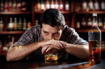 addiction alone: young alcoholic drunk man thinking of about alcohol addiction drinking indoors at bar of an irish pub leaning hands on whiskey glass in alcoholism concept