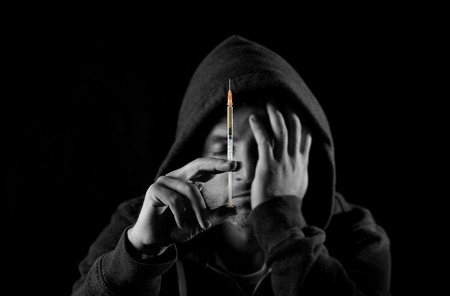 stoned:  black and white portrait of young sick drug addict man wearing hood holding heroin or cocaine syringe thinking and  looking wasted and depressed facing dope abuse and addiction