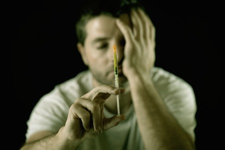 dope:  portrait of young sick drug addict man holding heroin or cocaine  syringe thinking and  looking wasted and depressed facing dope abuse and addiction  Stock Photo