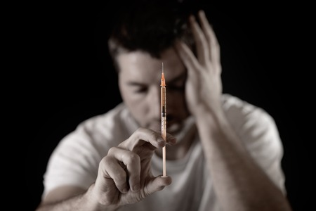 stoned:  portrait of young sick drug addict man holding heroin or cocaine  syringe thinking and  looking wasted and depressed facing dope abuse and addiction  Stock Photo