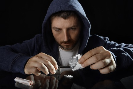 stoned: young drug addict man on hood alone ready preparing cocaine lines pouring gram bag on mirror with rolled banknote in moody and grunge lighting studio setting Stock Photo