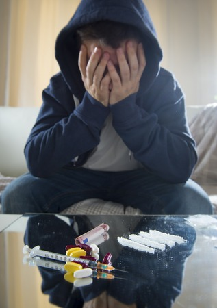 depressed man Cocaine addict, sniffing cocaine at home on his own sitting on the couch photo
