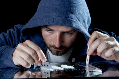 snort: depressed sick looking Cocaine addict man, sniffing cocaine using razor blade for cutting the drug and rolled banknote to snort the coke