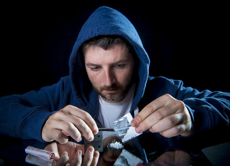 snort: depressed sick looking Cocaine addict man, preparing cocaine shot using razor blade for cutting the drug and rolled banknote to snort the coke Stock Photo