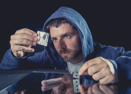 snort: depressed sick looking Cocaine addict man checking coke bag holding razor blade for cutting the drug and rolled banknote to snort the coke