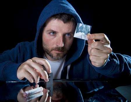 depressed sick looking Cocaine addict man checking coke bag holding razor blade for cutting the drug and rolled banknote to snort the coke
