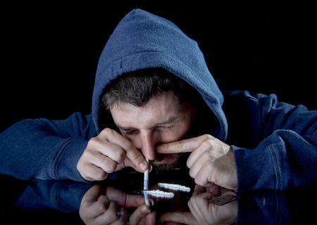 young drug addict man on hood snorting cocaine on mirror with rolled banknote at home alone isolated on black background photo