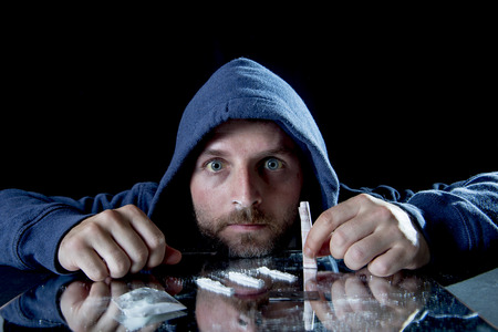 snort: depressed sick looking Cocaine addict man, sniffing cocaine with rolled banknote to snort the coke
