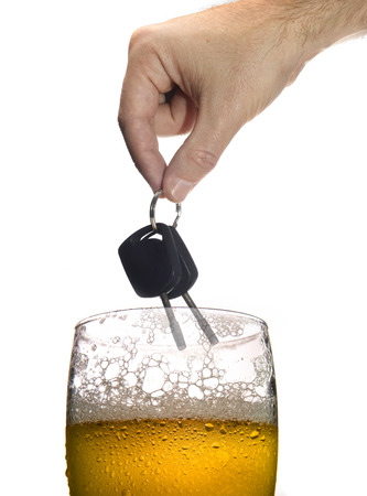 man hand holding car keys over glass of beer isolated on white background representing safety and about the danger of drinking alcohol and driving drunk photo