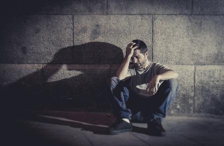 homme triste: blanc jeune homme perdu assis sur le sol de la rue avec des ombres sur le mur en b�ton se sentir mis�rable et triste en sc�ne urbaine repr�sentant la d�pression et la maladie