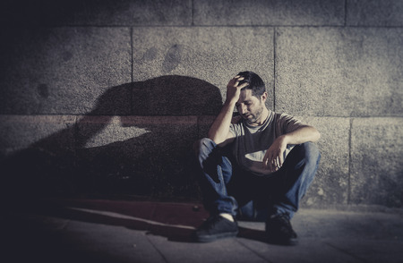 sad lonely: white wasted young man sitting on street ground with shadow on concrete wall feeling miserable and sad in urban scene representing depression and sickness