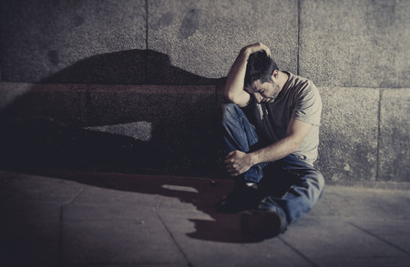 white wasted young man sitting on street ground with shadow on concrete wall feeling miserable and sad in urban scene representing depression and sickness photo