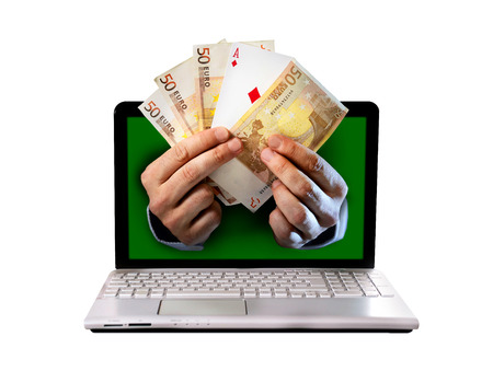man hands comming out computer screen holding euro banknotes and ace poker playing cards in online or on line and  internet casino gambling and bets concept isolated on white background photo