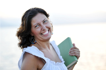 happy attractive mature woman on her 40s holding a book smiling at the beach outdoors portrait in front of the sea enjoying a relaxing summer evening in calm  Stock Photo