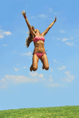 happy young blond attractive woman in pink bikini jumping to the air free on cyan blue summer sky in vitality , fitness , freedom and healthy lifestyle concept Stock Photo