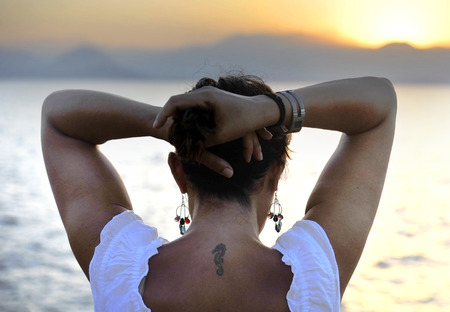 attractive 40s mature woman on her back with little seahorse tattoo standing alone on the beach thinking looking at sea horizon pensive and thoughtful on relaxing and peaceful summer sunset enjoying vacation