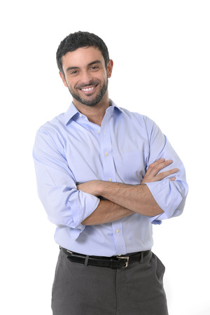 young attractive business man standing in corporate portrait isolated on white background smiling with folded arms in shirt and suit trousers photo