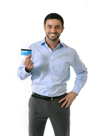 young attractive smart casual man wearing blue shirt showing credit card smiling happy isolated on white background in financial sucess, online shopping, e-commerce and banking concept photo