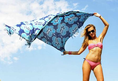 beach wrap: young sexy blonde girl holding beach wrap to the air playing with the cloth and the wind against a vivid blue sky in relax enjoying summer holidays feeling free Stock Photo