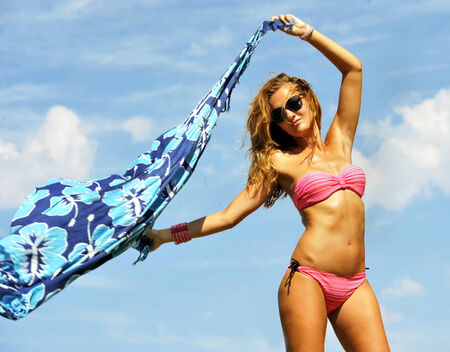 beach wrap: young sexy blonde girl holding beach wrap to the air playing with the cloth and the wind against a vivid blue sky in relax and freedom enjoying summer holidays  Stock Photo