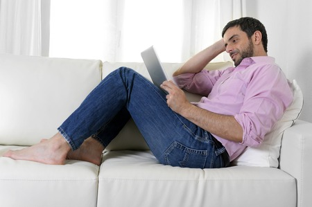 young happy attractive man using digital pad or tablet sitting on couch at home connected to internet reading , watching the screen and smiling pensive wearing casual pink shirt and jeans photo