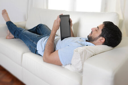 young happy attractive man using digital pad or tablet lying relaxed on couch at home connected to internet reading , watching the screen and smiling pensive wearing casual blue shirt and jeans photo