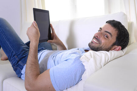 young happy attractive man using digital pad or tablet lying relaxed on couch at home connected to internet reading , watching the screen and smiling pensive wearing casual blue shirt and jeans