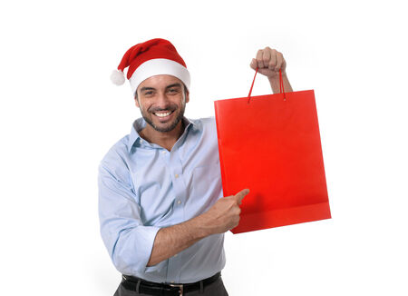 happy young attractive man wearing santa hat holding and pointing red shopping bag in christmas consumerism , sale, buying and xmas gifts and presents concept isolated on white background photo