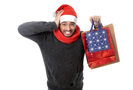 young attractive shopaholic man wearing santa hat holding a lot of shopping bags looking desperate and in stress in christmas consumerism, sale, compulsive buying, spending money and xmas gifts and presents concept isolated on white background
