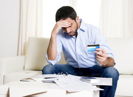 credit crisis: young attractive latin american business man worried in stress paying bills holding credit card sitting on  sofa at home in financial problems