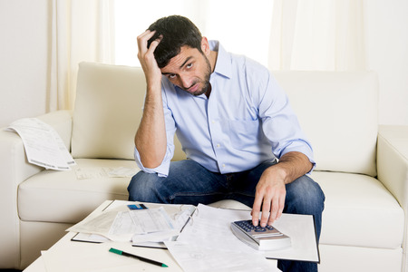 jeune, séduisant latino-américain homme d'affaires inquiet dans le paiement des factures de stress tenant carte de crédit assise sur le canapé à la maison à des problèmes financiers Banque d'images