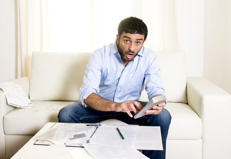 young attractive latin american business man worried in stress paying bills holding credit card sitting on  sofa at home in financial problems  photo